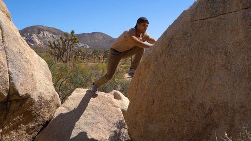 A Man Climbs On A Boulder Of Rock