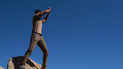 Man On A Rock Giving Instructions Through Hand Signs