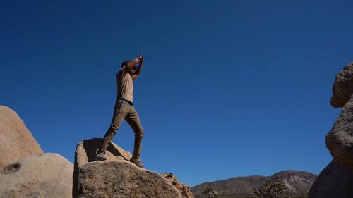 Low Angle Footage Of A Man Standing On A Boulder Waving To Signal Or Call For Attention