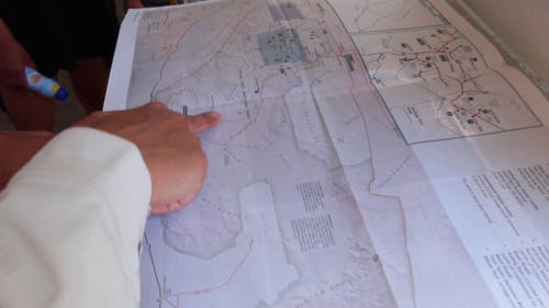 A Person Discussing Details Using A Map