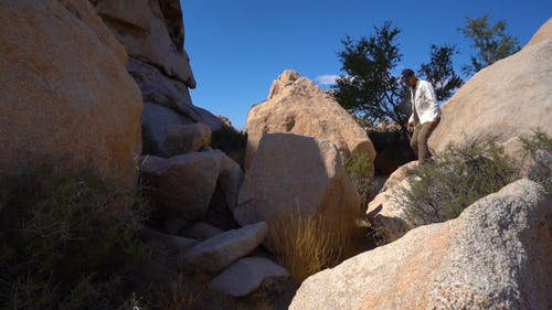 Man Stepping On Rocks And Boulders To Cross