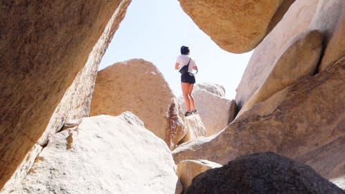 Low Angle Footage Of The Back View Of A Woman In Shorts And T-shirt  Standing On A Boulders Taking Pictures,
