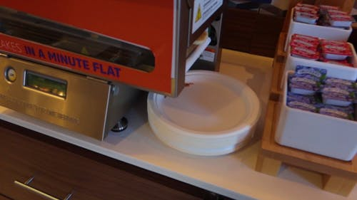 Close- Up Of A Pancake Making Machine Dispensing A Pancake On A Stack Of Paper Plates Beside Boxes Of Jellies On A Counter Top In Slow Motion