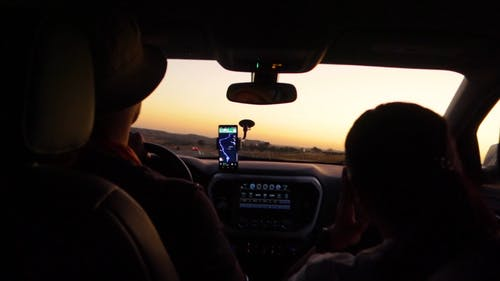 Slow Motion Footage Of Two People Traveling In A Vehicle Using A Navigational Assistance From A Smartphone