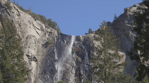 Low Angle Footage Of A Water Fall Flowing Down The Rocky Mountain Cliff
