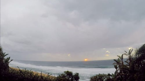 Sun Rising Over The Sea Horizon Before Hiding Over Thick Clouds Formation