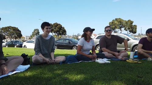 A Group Of People Gathered In A Park To Do Meditation Exercise