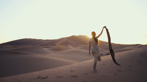 Slow Motion Footage Of A Woman Holding Up Her Arm With A Scarf On Hand Walking Barefoot On Desert Sand On A Windy Day