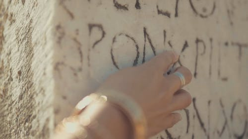 "Slow motion footage Of A Woman""s Fingers Touching A Stone wall With Carved Ancient Script"