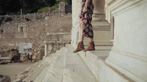 A Woman Walking Down The Steps From An Ancient Temple Ruins