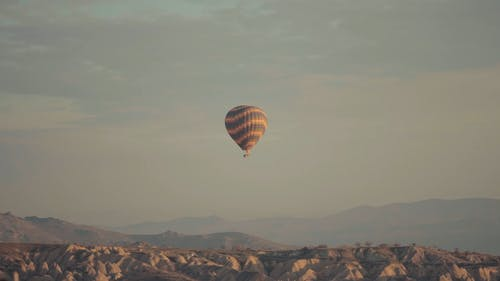 A Hot Air Balloon Flying Over The Desert Hills And Mountains