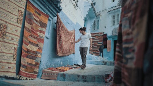 Slow Motion Footage Of A Man Walking Down The Steps Of An Alley Looking At Carpets Of Assorted Designs Hanging On Walls