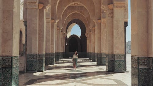 Slow Motion Footage Of A Woman Walking On Beautifully Tiled Hallway Between Huge Columns