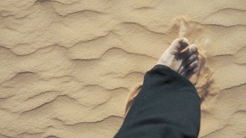 Man Walking Barefoot On Desert Sand