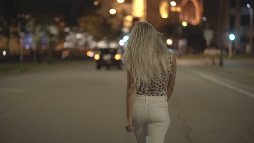 Slow Motion Footage Of A Young Woman With Long Blonde Hair Looking Over Her Shoulder And Turning While Happily Walking In The Street At Night