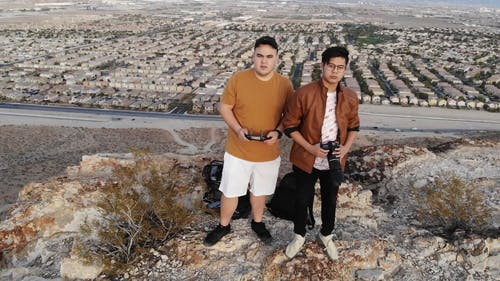 Drone Footage Of Three People On Top Of A Rocky Mountain With The View Of Its Surrounding Landscape