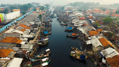 Aerial Footage Of A Boats Going In And Out A Narrow Canal With Its Banks Lined With Structures Leading To A Open River