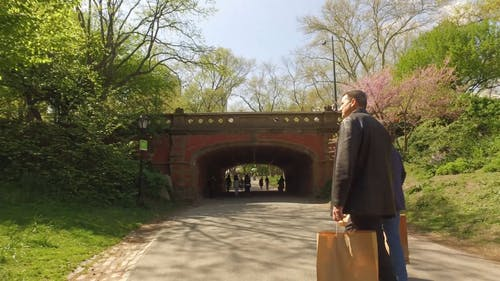 Two Men Walking Through A Tunnel Towards The Park