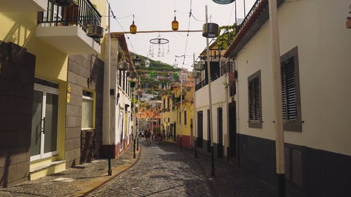 A Group Of People Walking In A Cobblestone Alley With Assorted Pendant Lights Hanging Between Buildings At Daytime
