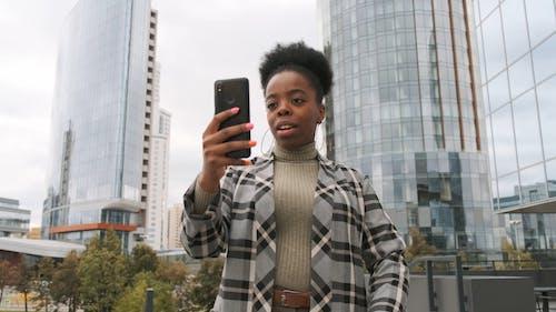 Una Mujer En Una Videollamada Fuera De Un Edificio