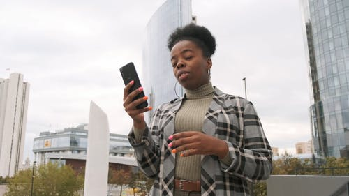 A Woman In A Video Call Outside Shows The Building Besides Her