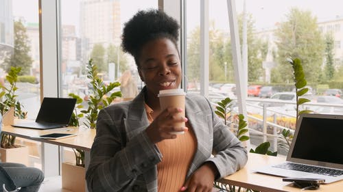 A Woman Leaning On A Counter Table With Laptops Enjoying A Drink From A Take-out Coffee Cup
