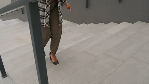 A Woman Talking On Her Cellphone Walking Up The Stairs
