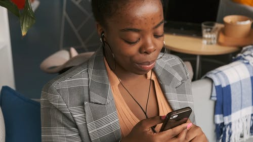 A Woman Seated Inside A Coffee Shop Using Her Cellphone