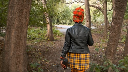 Backside Of A Woman Walking Out Of The woods Towards The Road