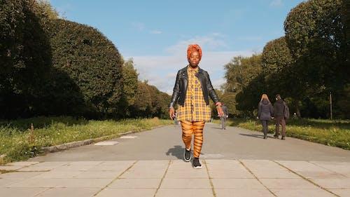 Женщина, идущая по бетонной дорожке, прикрывает глаза от лучей солнца