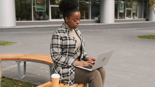 A Woman Seated On An Outdoor Bench Works On Her Laptop