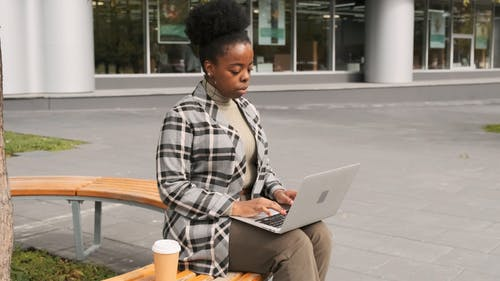 A Woman Seated On An Outdoor Bench Have A Sip Of Coffee While Working On Her Laptop