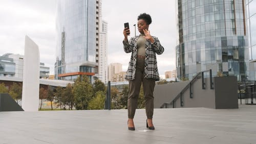 A Standing Woman On A Video Call On Her Cellphone Outside Of The Building