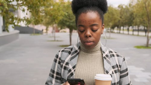 A Woman Walking Uses Her Phone While Holding A Cup Of Drink
