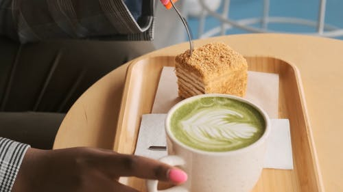 Close-up Of A Woman Enjoying Eating A Cake Beside A Cup Of Latte On A Wooden Tray In Slow Motion