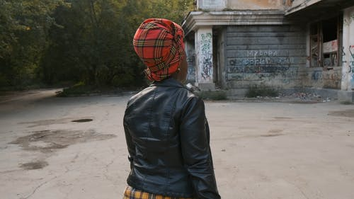 A Woman In Leather Jacket Walking Around An Abandoned Property
