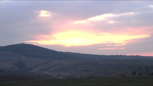 Time Lapse Footage Of A Cloud Formation Covering The Sun Over Vast Green Land And A Mountain