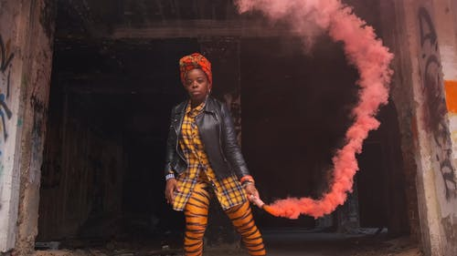 A Woman Dispensing A Smoke Screen Inside An Abandon Building