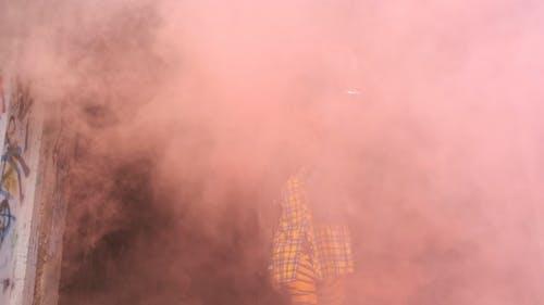A Woman Dancing Behind A Dispensed Smoke Screen
