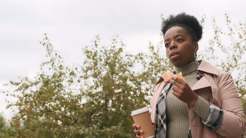 Slow Motion Footage f A Woman Walking Outdoor Eating A Sandwich And Drinking Take-OUT Coffee