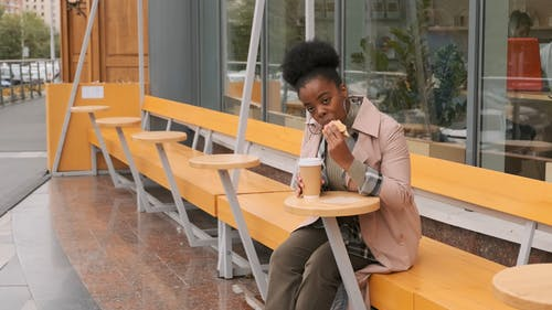 A Woman Eating Snacks Outside Of A Cafe