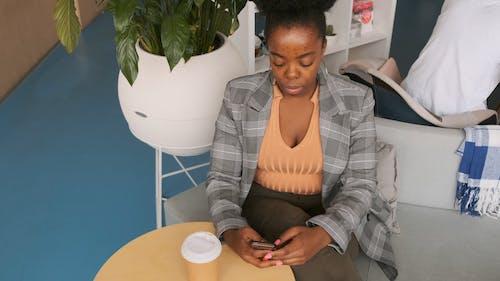Una Mujer Sentada Usando Un Teléfono Celular En El Interior