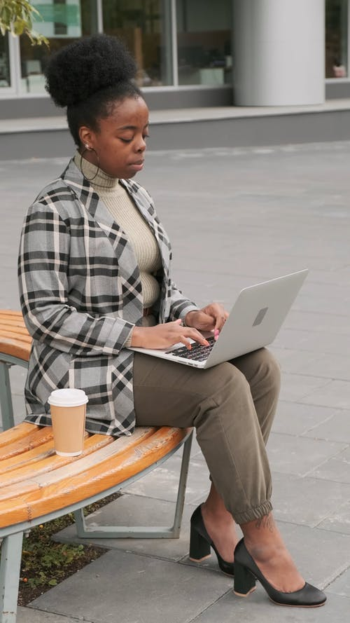 A Woman Seated On A Bench Drinks Her Coffee While Working On Her laptop