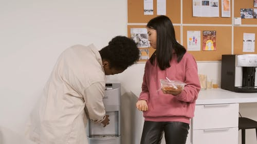 Two Women Having Their Food And Drink In The Workplace Pantry