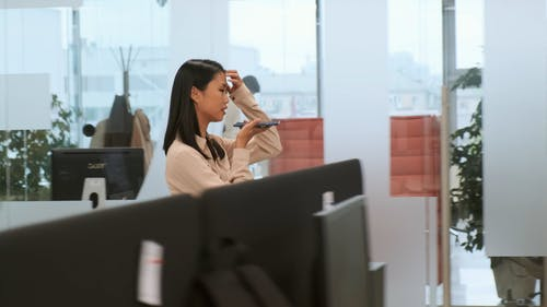 A Woman Talking Through The Speaker On Her Cellphone While Walking Inside The Office