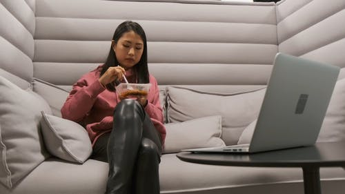 A Woman Monitoring Her Laptop While Eating In A Sofa