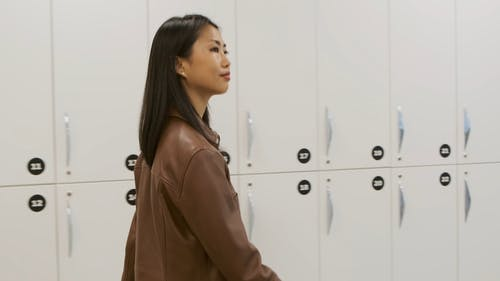 A Woman In Leather Jacket  Walks By The Wall Of Lockers
