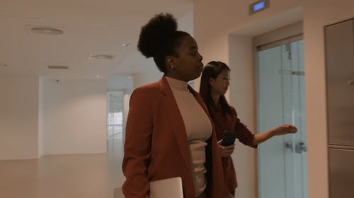 Two Women In Discussion Walks In An Elevator