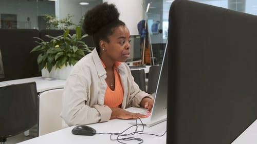 A Seated Woman Is Busy Working On A Computer