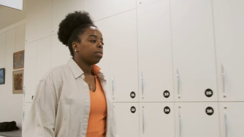 A Woman Walking Pass The Lockers In Row